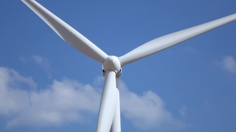 Wind turbine rotates blades against the background of sky. Close up