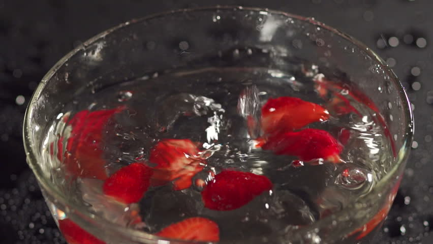 Close-up of a strawberry falling into a bowl with water, slow motion. Strawberry dropping into a bowl of water creating splashes. | Shutterstock HD Video #30006085