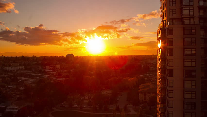Time Lapse of Sunset in a Residential Area with Houses and Apartment. Sun light reflecting from apartment building as it setting down the horizon