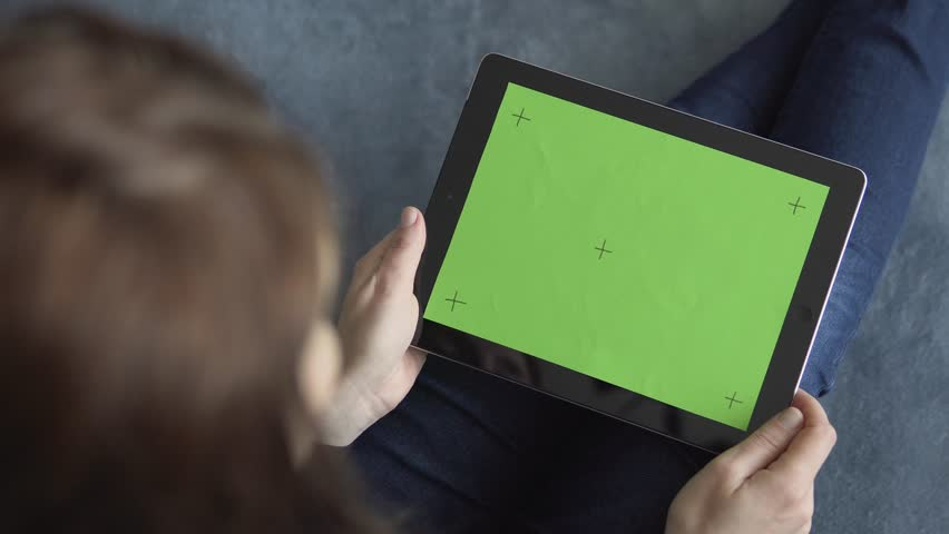 Girl sitting on blue sofa is holding a tablet pc with green screen and markers, making pick gestures on touchpad, 4K | Shutterstock HD Video #30017425