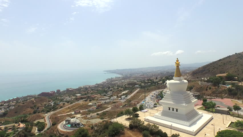 Aerial overhead rotating view of a religious Buddhist temple in Spain. This full perspective of the monument in front of the ocean view over malaga city. 4k 30fps video June 7, 2015.   Shutterstock HD Video #30037975