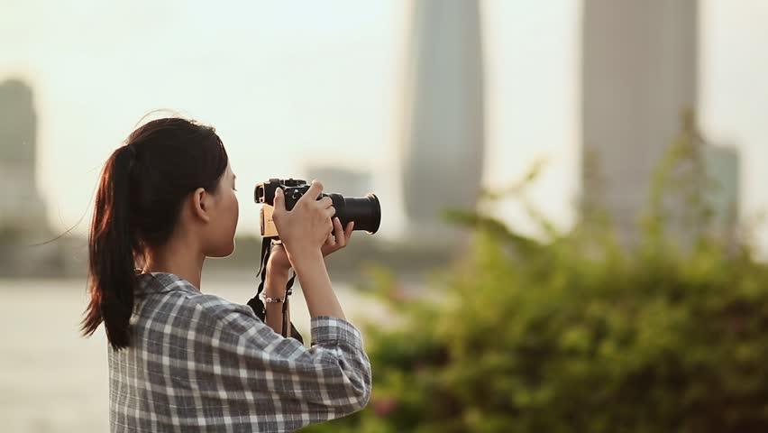 Vietnamese girl photographer takes pictures of nature in the city center at sunset