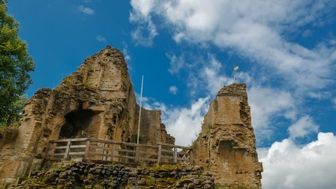Tilting shot of the Knaresborough Castle progressively lit by beautiful sunlight against a dramatic sky in Yorkshire, England, UK