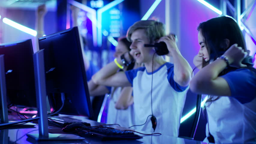 Team of Teenage Gamers Win Internet Cafe Online Video Gaming Tournament and Celebrate with High-Fives. Shot on RED EPIC-W 8K Helium Cinema Camera.