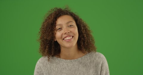Happy smiling young multi ethnic millennial woman talking over video chat conference call on green screen. On green screen to be keyed or composited.