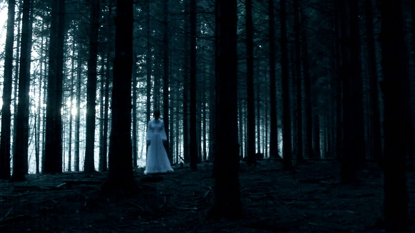 Mysterious woman in the white dress in walking in the dark spooky forest