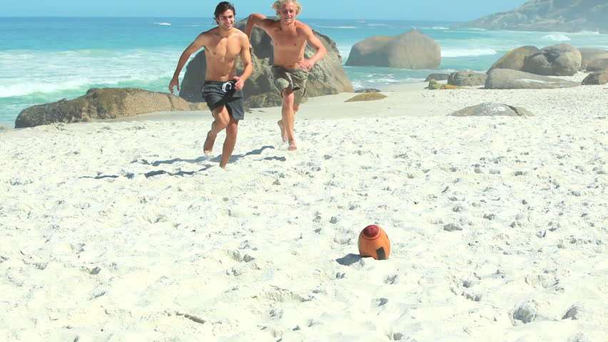 Two guys running with a rugby ball at the beach