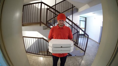 Delivery boy in a red uniform holding a stack of pizza boxes making a home delivery as seen through a spyhole. Shot with a fisheye lens.