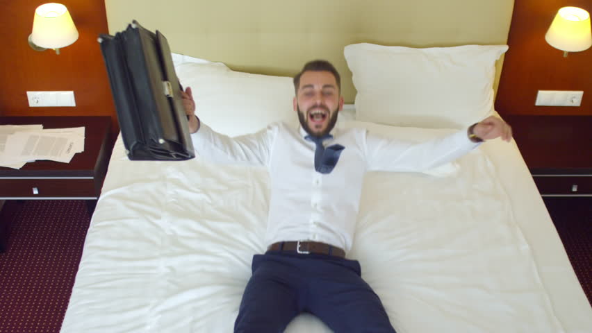 High angle view of young happy businessman jumping and falling on hotel bed with briefcase, lying and smiling