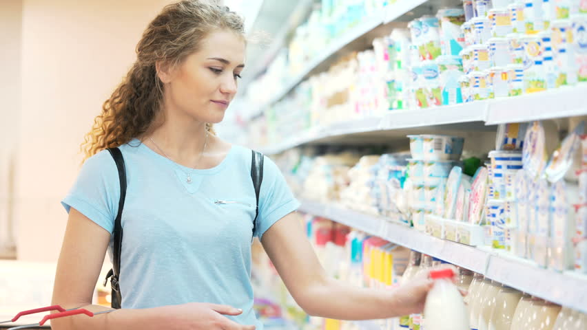 One female mistress alone look for milk freshness quality ingredient in town marketplace. Smile attractive cute pretty person 30s carefully read sticker, pick up bottle and puts to products bag | Shutterstock HD Video #30104995