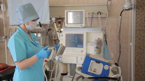 A female nurse prepares a defibrillator for a surgical operation. New medical technologies