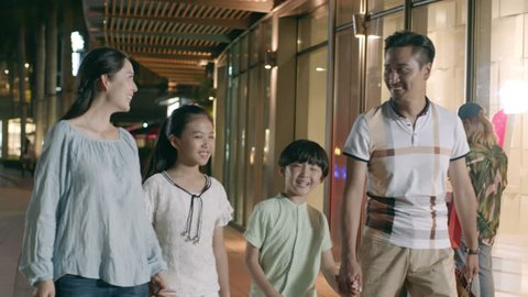 asian family of 4 walking & shopping outside a shopping mall at night in slow motion
