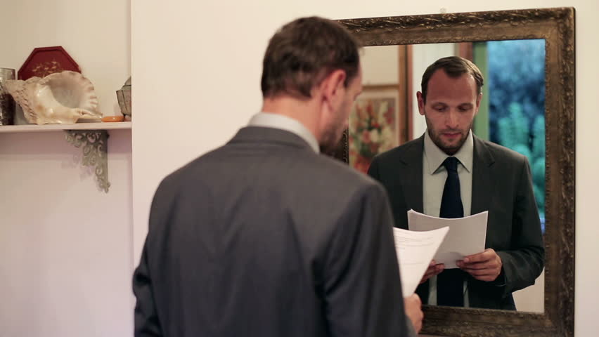 Young businessman practice his speech in front of mirror