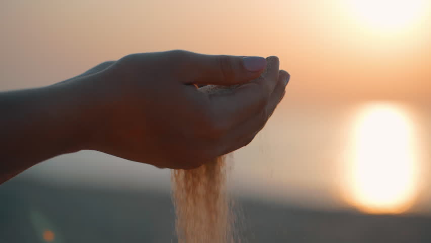 Close up of woman pouring sand running through fingers slow motion at the beach with sun flare and blue sky. Beautiful scene of young lady playing with sand on sunrise or sunset.