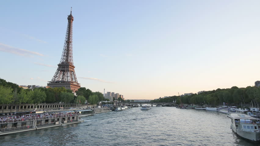 Eiffel Tower in Paris Time Lapse from Day to Night. The Eiffel tower building is a wrought iron lattice tower on the Champ de Mars in Paris. Typical landmark of bridges and boats over the Seine.  | Shutterstock HD Video #30188791