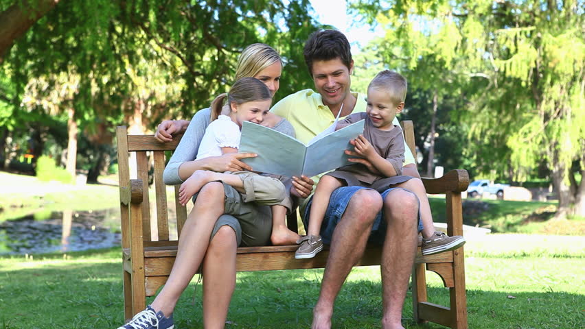 Video Bench Part - 16: Video Of A Family Sitting On A Bench Reading A Book - HD Stock Video Clip