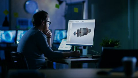 Young Bearded Engineer Works on a 3D Model Of Industrial Turbine. It's Late at Night He's the Only One Left on the Dark Office. Shot on RED EPIC-W 8K Helium Cinema Camera.