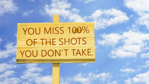 You miss 100% of the shots you don't take, Words on a wooden sign against time lapse clouds in the blue sky.