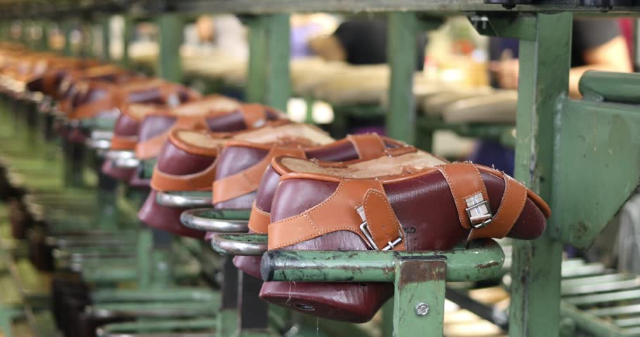 Shoes move on conveyor in factory, people out of focus, close-up, slow motion