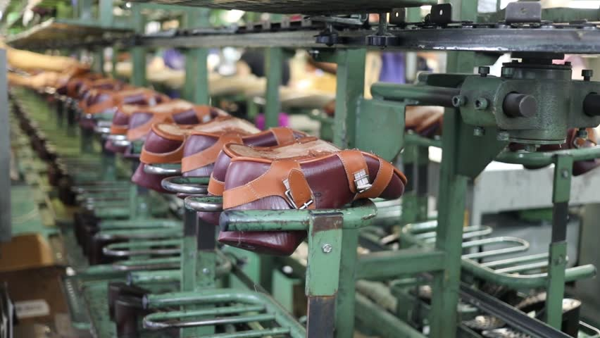 Shoes move on conveyor in shoes factory, people out of focus, slow motion