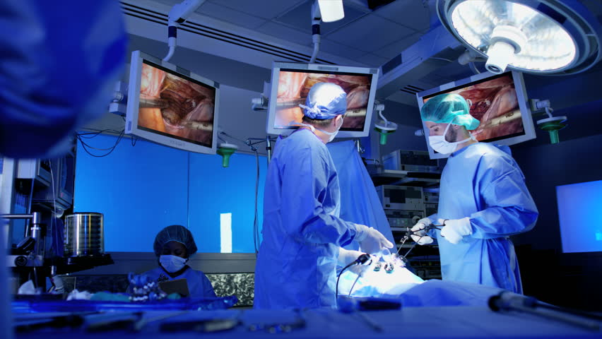 Laparoscopic operation in surgical theatre using Endoscopy monitor technology while African American Anesthesiologist nurse assists wearing protective clothing RED WEAPON | Shutterstock HD Video #30251788