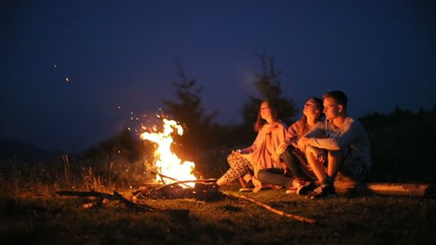 Young people sitting fire camp looking sky night outside nature pointing finger stars romantic having rest friends girls boy woman man three persons bonfire camping silence calm summer holidays warm