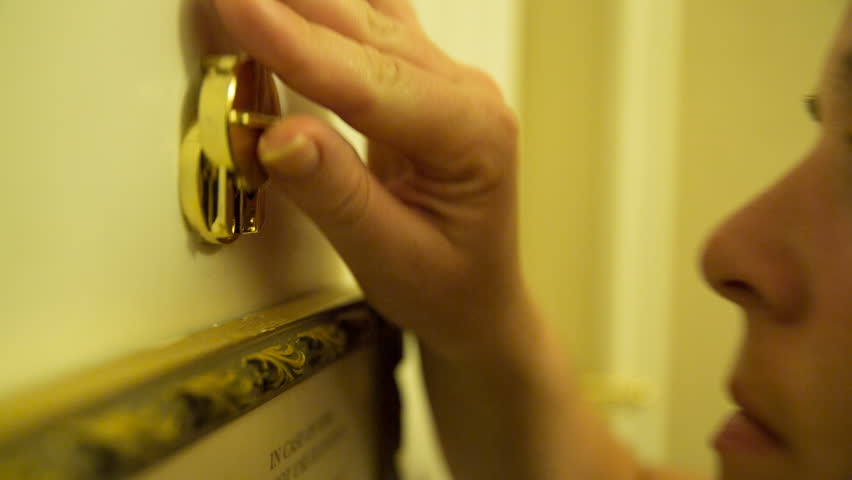 Hotel Peephole Look Through Follow Hand to Door Lock. a woman looks through a hotel peephole then the view follows her hand as she locks the door latch for extra security