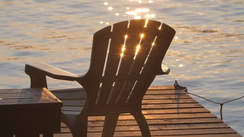 Slow motion golden sparkles from lake with dock and Muskoka chair. Summer in cottage country, Ontario, Canada.
