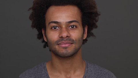 Closeup young dark-skinned male with afro haircut nodding positively isolated over charcoal backgroun