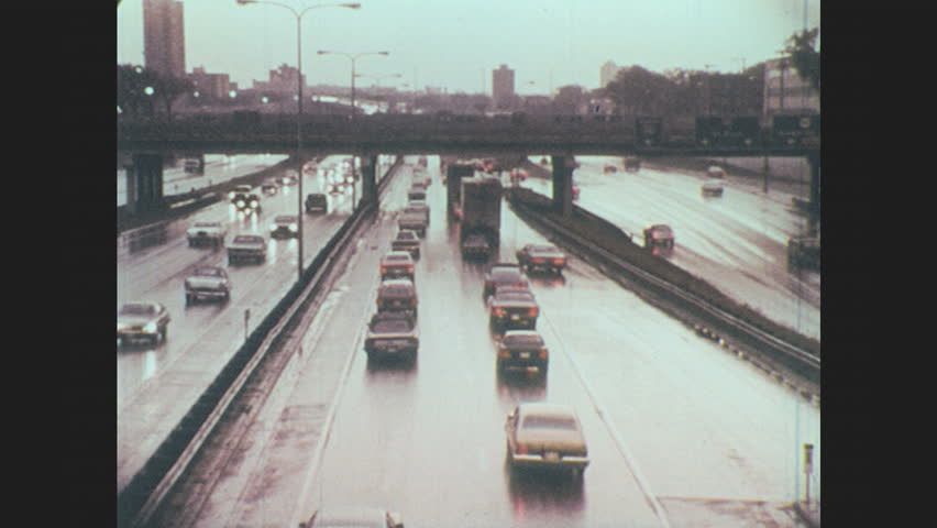 1970s: Tire rolls on wet pavement. Car drives down rainy interstate. Speedometer. Car skids into path of oncoming car.