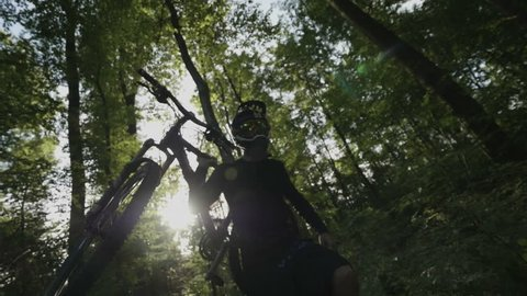 Mountain biker carries his bike through forest in super slow motion