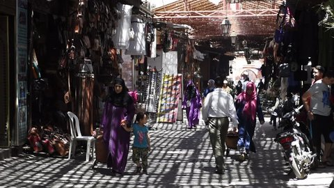 MARRAKECH, MOROCCO - MAY 9 2017: Unidentified people walk in the multicolored souk. The souk is a traditional market with all kind of handmade craft