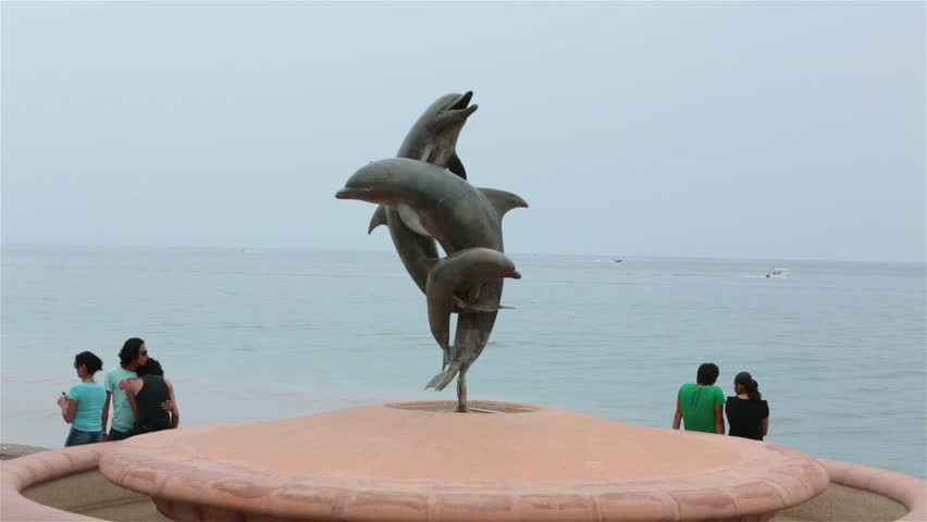PUERTO VALLARTA, MEXICO - CIRCA NOV 2012: Teenagers at Friendship sculpture. Boardwalk Malecon beach and tourist area on Banderas Bay, Pacific Ocean. Cultural artistic center. Gay couple holding each other.