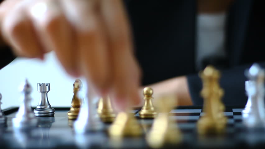 Close up shot hands of man and business woman moving gold king chess to kill silver king chess on chess board game for winner and loser business challenge metaphor and business competition concept