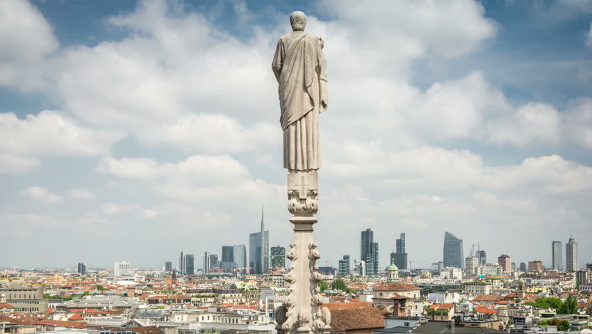 Panoramic view of Milan from the rooftop of the Duomo di Milano. City skyline. White clouds move fast across the blue sky. Time lapse video. | Shutterstock HD Video #30365665