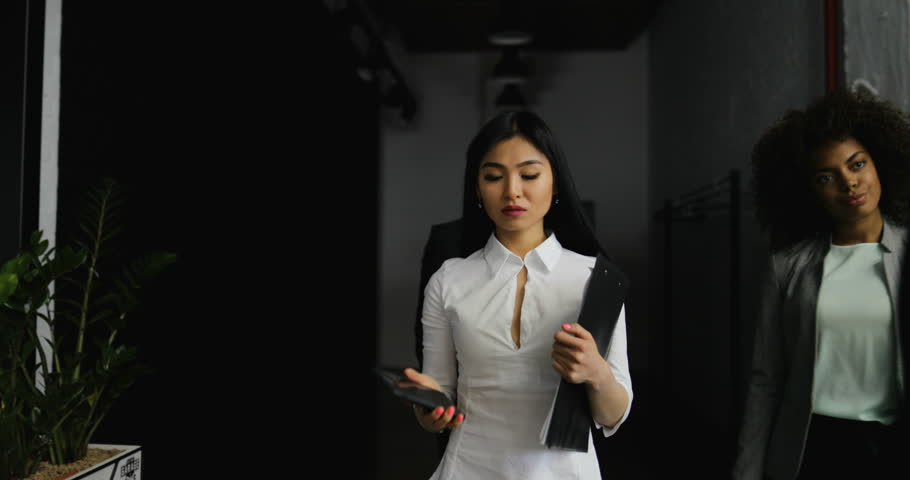The development group of a project standing and discussing the asian businesswoman make phone call while walking with business people team in creative office successful mix malvernweather Choice Image