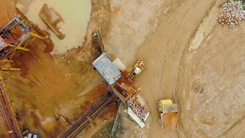 Excavator loader working at sand mine.  Aerial view of mining equipment at sand quarry. Mining conveyor and sand work in sandpit