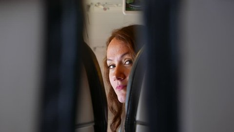 Young woman quickly look back between airliner seats, glance to stranger behind her. POV camera watch in gap, see face and eyes of pretty coquettish girl passenger ahead.
