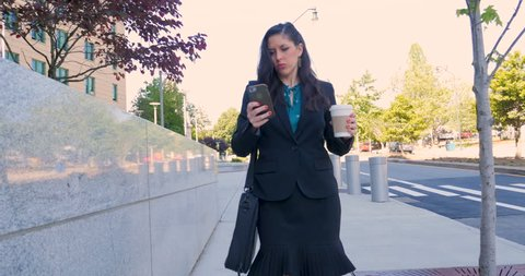 Hurried attractive businesswoman walking and multi tasking with smart phone down steps and in street with togo coffee cup in 4k