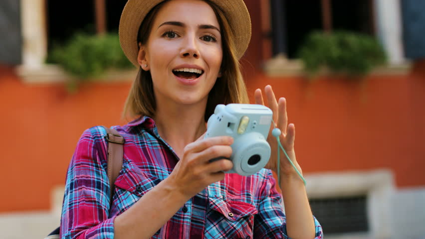 Beatiful woman in the hat taking pictures on the stylish blue camera on the orange wall background. Close up.