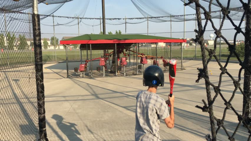 Boy in batting cage swinging at mechanically pitched balls and hitting one before shaking his hand after bat shock waves.