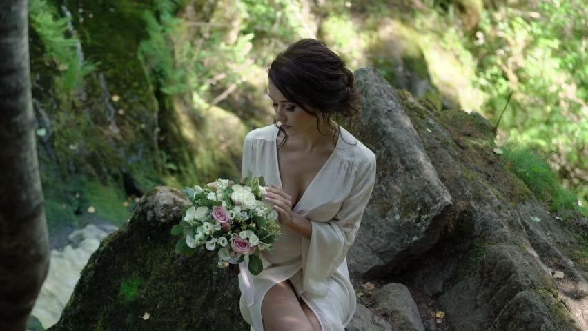 Young woman sitting on a rock near waterfall in lingerie | Shutterstock HD Video #30427414