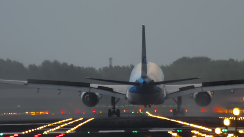 The wide-bodied aircraft lands on the illuminated runway in the early morning
