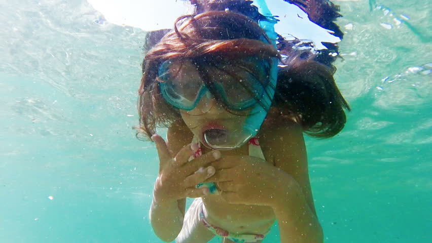 Little girl with fins, mask and snorkel swimming in the sea, gopro underwater footage
