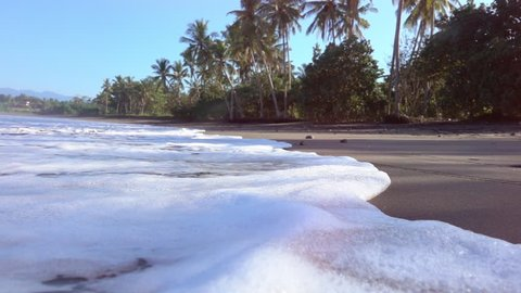SLOW MOTION CLOSE UP LENS FLARE: Foamy ocean waves washing black sandy beach on paradise island in tropics. Swash wave traveling up the gorgeous sea shore with lush palm trees in sunny Bali, Indonesia