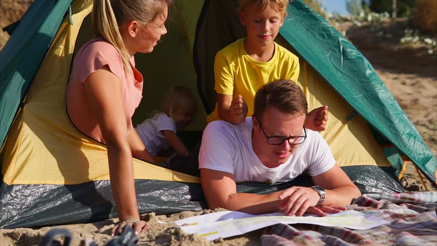A young family who came to rest create a route for their travel, they look at the paper map, people are in a tent, children play with their father, mother lovingly looks at what happens on the weekend