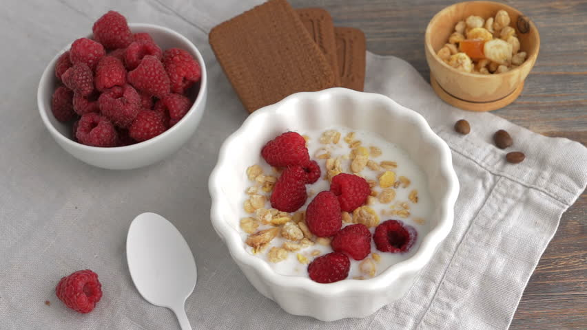 Healthy breakfast - yogurt or milk with raspberry berries, cereals or gorp, chocolate cakes. Top view. Camera locked down. Selective focus. | Shutterstock HD Video #30532375