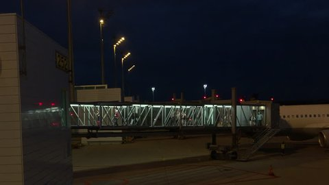Passengers disembarking airplane via aerobridge (Jet Bridge) at Munich International airport, Germany. Prores