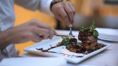 Attractive young man tastes foie gras with sauce