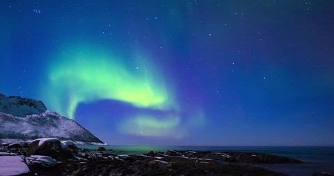 Northern Lights, polar light or Aurora Borealis in the night sky time lapse over Senja island in Northern Norway.